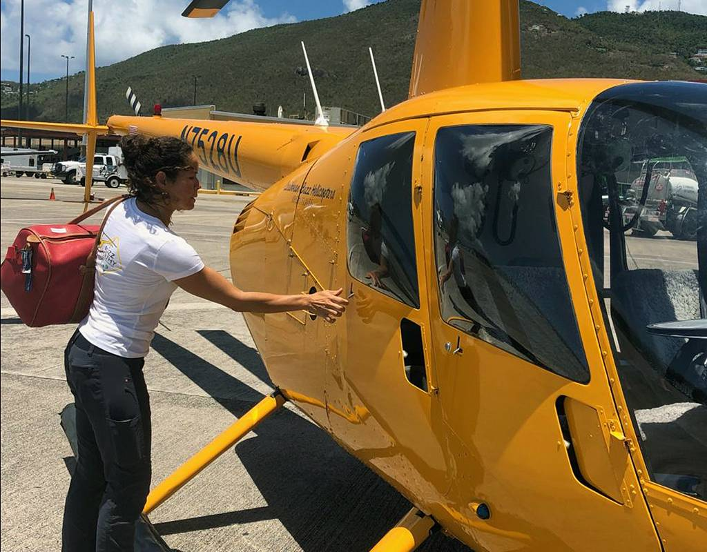 Maria Rodriguez, owner of Caribbean Buzz Helicopters, loads a bag into the company's Robinson R44, painted its signature yellow. Dan Parsons Photo