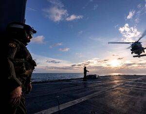 Lieutenant Commander Matthew Schroder, left, observes the departure of a U.S. Navy MH-60R from HMAS Ballarat's flight deck during Exercise Malabar. Leading Seaman Shane Cameron Photo
