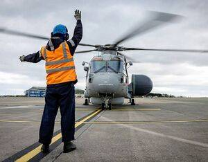 Leading Seaman Paul Rendle signals to the first Crowsnest helicopter to take off. Royal Navy Photo