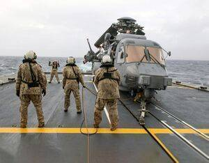 Crew members guide a CH-148 Cyclone helicopter into position aboard HMCS Fredericton during Operation Reassurance. Cpl Simon Arcand/RCAF Photo